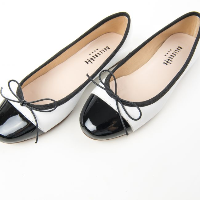 White leather ballet flats and black patent toe