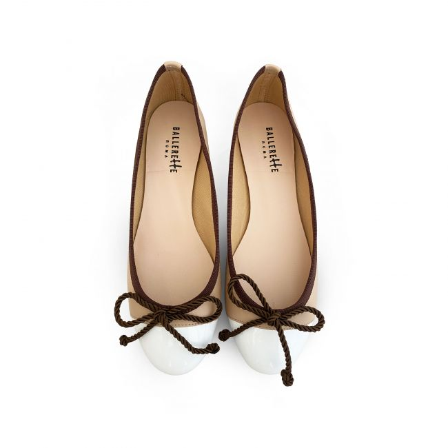 Beige leather ballet flats with white patent toe and brown ribbon